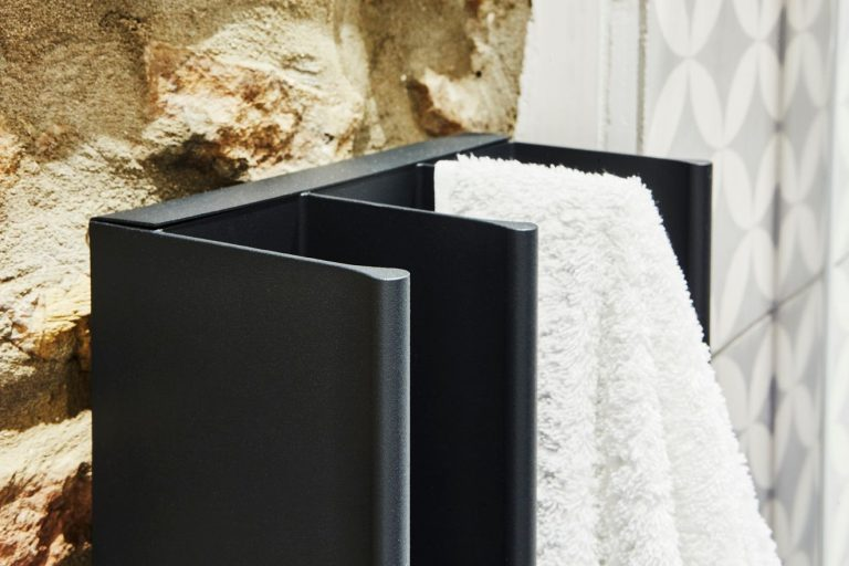 Gordon Heated Towel Rail on a rock wall with a white towel